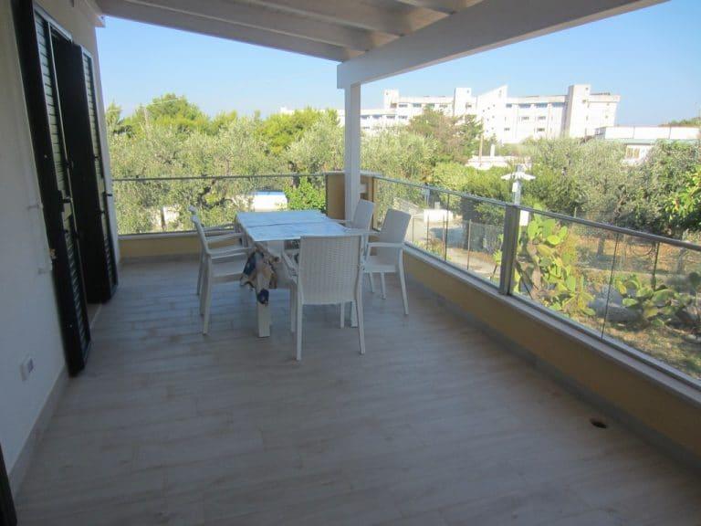 Ampia veranda con tavolo e sedie da giardino