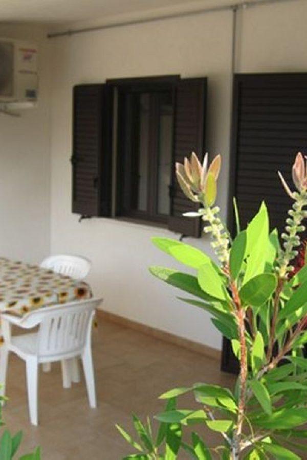 Veranda coperta con tavolo e sedie da giardino